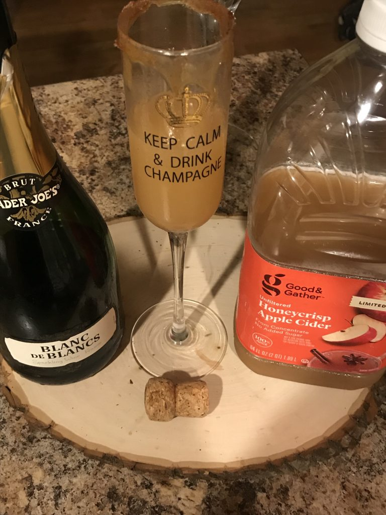A tall glass of apple cider mimosa made with champagne and a rim dipped in cinnamon sugar and caramel syrup